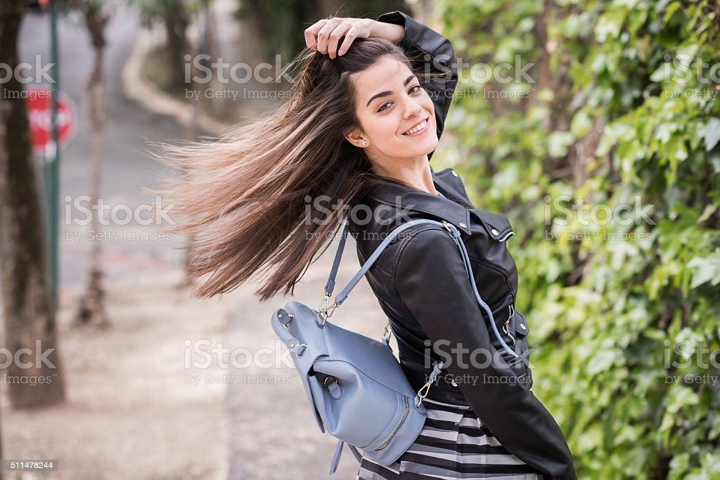 Young woman moving her hair in urban background stock photo
