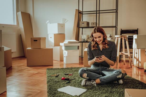 jeune femme se déplaçant à un nouvel appartement. taper un message tout en asseyant sur un tapis - génération z photos et images de collection