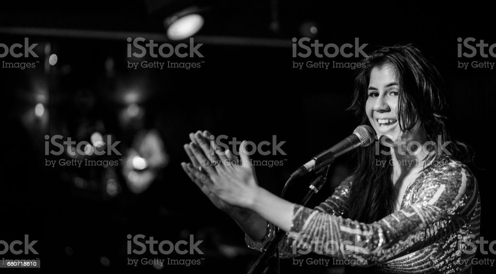 Young woman, musician, singer and performer, singing on the stage. stock photo