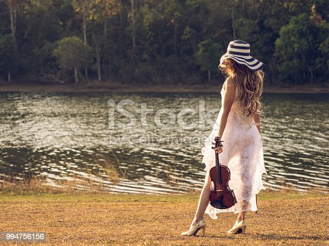 istock Young woman musician/violinist on white dress holding violin over river/park/forest, freedom lifestyle music vintage tone concept. 994756156