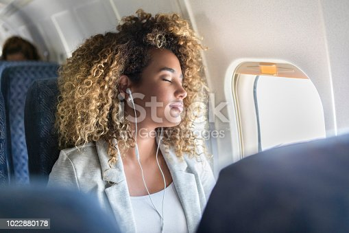 istock Young woman napping during flight 1022880178