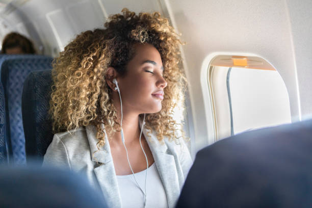 Young woman napping during flight stock photo
