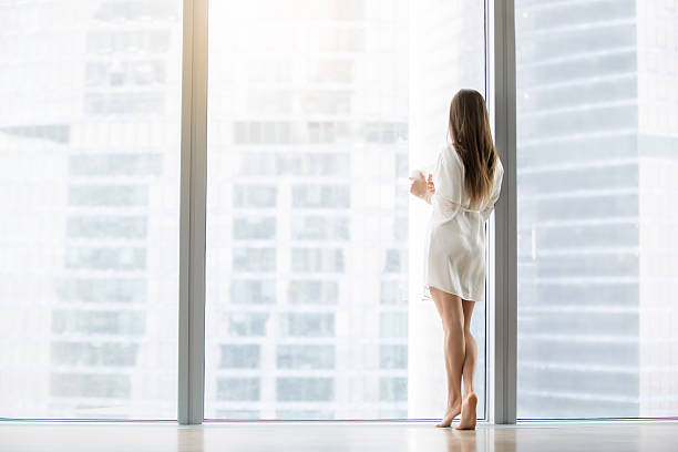 Young woman near the floor window stock photo