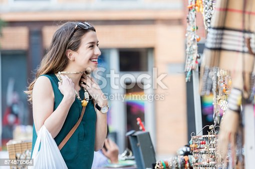 A smiling young woman holds a necklace up to herself in an outdoor street shop in New York City.  She is haggling with an unseen shop keeper.