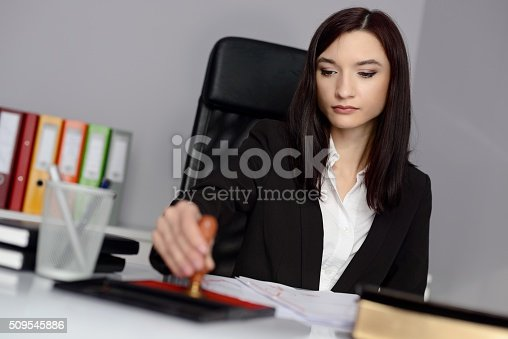 854317150istockphoto Young woman notary public reaches her stamp 509545886