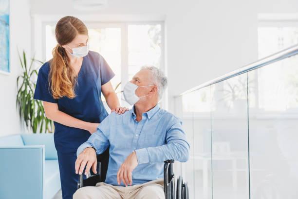 ung kvinna sjuksköterska förklara information till mannen patienten i rullstol i medicinsk ansiktsmask medan du talar tillsammans på sjukhus. epidemi- och virusbegrepp - hemvårdare bildbanksfoton och bilder