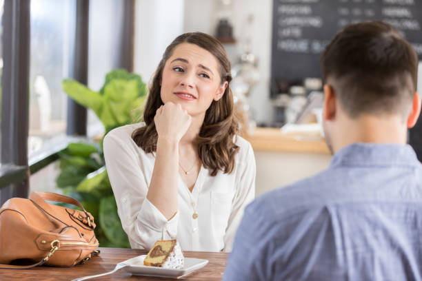 Young woman on a bad blind date Young woman makes an uneasy or disinterested face while on a blind date in a coffee shop. The back of the young man's head is seen in the foreground. bad date stock pictures, royalty-free photos & images