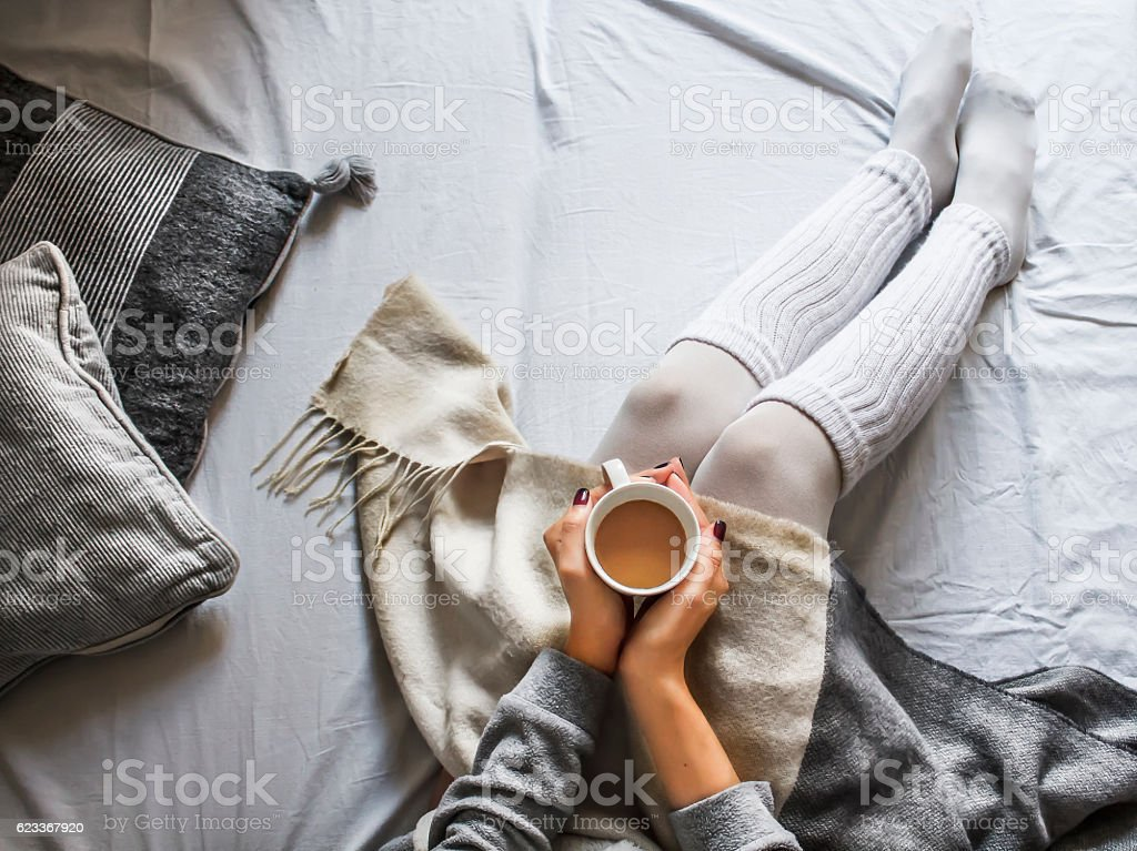 young woman on a bad holding a cup of coffee