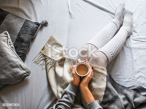istock young woman on a bad holding a cup of coffee 623367920