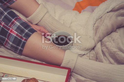 618750646 istock photo Young woman on a bad holding a cup of coffee 898425748