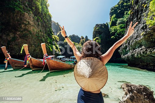 Young woman on a beautiful beach in Thailand with longtail boats, Phi Phi Island