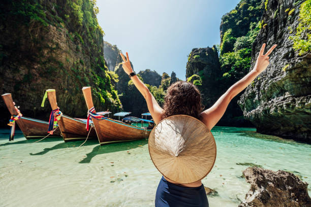 Young woman on a beautiful beach in Thailand with longtail boats, Phi Phi Island stock photo