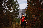 Young woman hiking in the beautiful outdoors. She is enjoying the autumn nature, wearing sports clothes. Getting ready for the adventure, she's following the footpath through the forest on a nice sunny day.