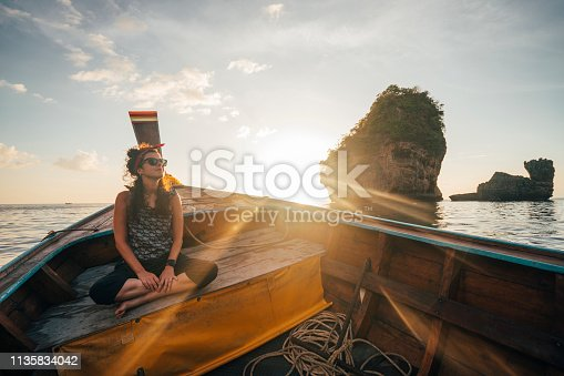 Young woman on a longtail boat in Thailand during sunset, Phi Phi Island