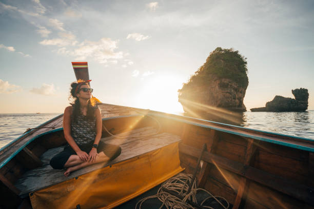 Young woman on a longtail boat in Thailand during sunset, Phi Phi Island stock photo