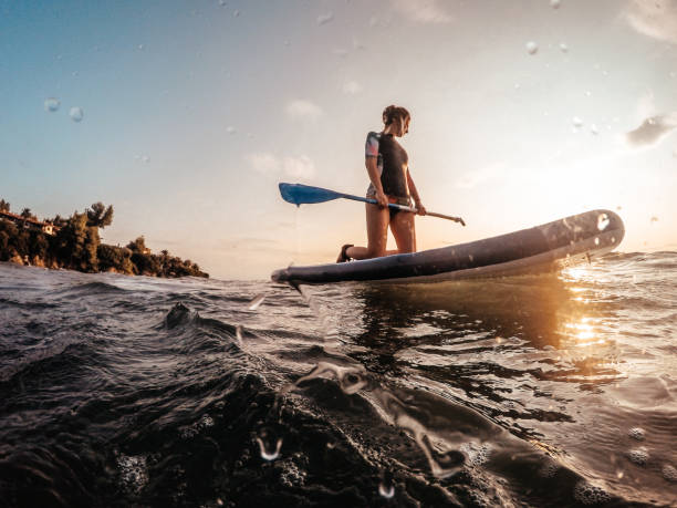 Young woman on a paddle board Photo of a young woman floating in the ocean on her paddle board  at sunset wetsuit stock pictures, royalty-free photos & images