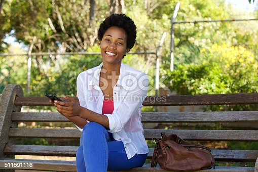 istock Young woman on a park bench with a cell phone 511591116