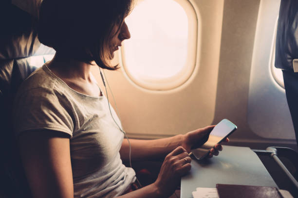 Junge Frau im Flugzeug mit Smartphone in der Hand – Foto
