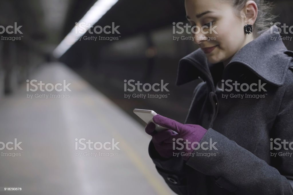 Young woman on a railroad station using a smart phone stock photo