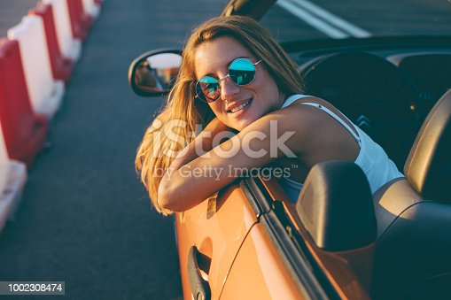 832085296 istock photo Young woman on a road trip with cabriolet 1002308474