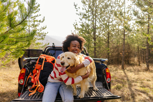 Photo of young smiling woman on a road trip with her best friend, her retriever dog, riding along on their pick up truck