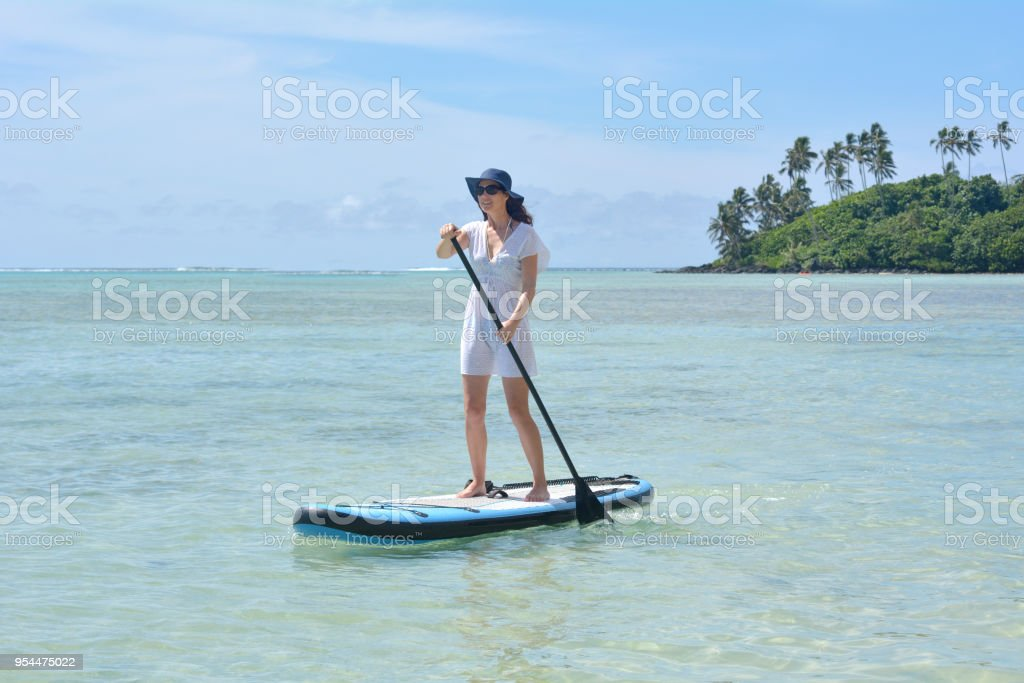 Young woman on a Stand Up Paddle Board paddle boarding in Muri lagoon...