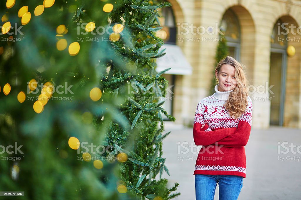 Young woman on a street of Paris decorated for Christmas royalty-free stock photo