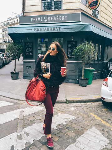 Paris, France - April 28, 2016: Fashionable young woman is walking on the zebra crossing with the Vogue magazine underarm and a cup of coffee