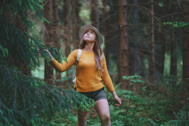 young woman on a walk outdoors in forest in summer nature, walking. - forest bathing foto e immagini stock