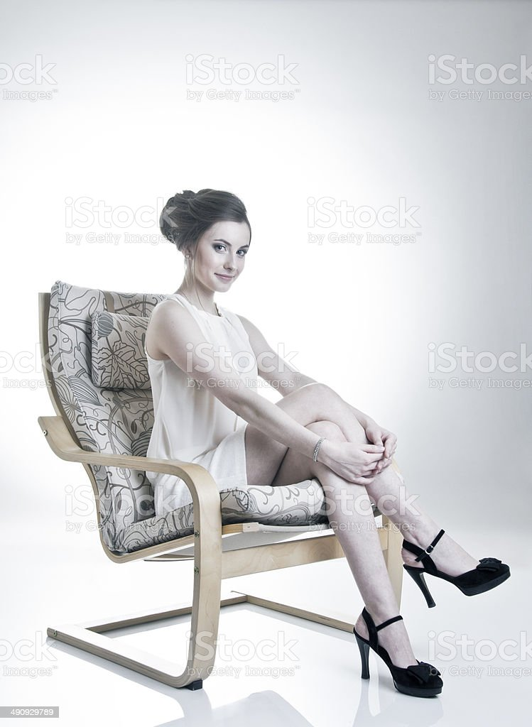 Young woman on arm chair stock photo