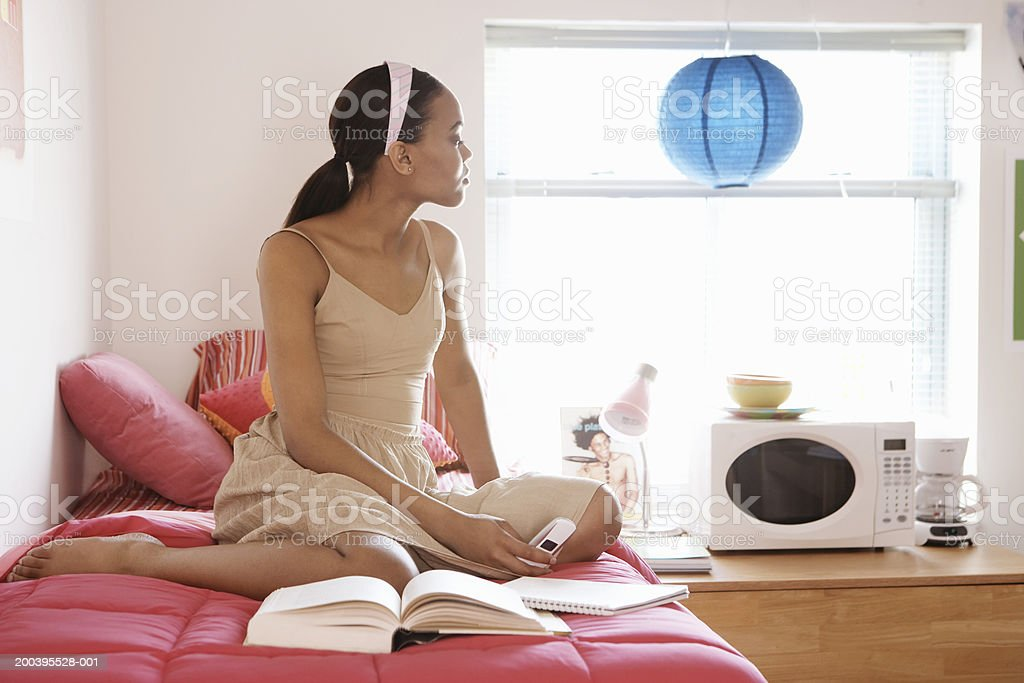 Young woman on bed looking out window in dorm room stock photo