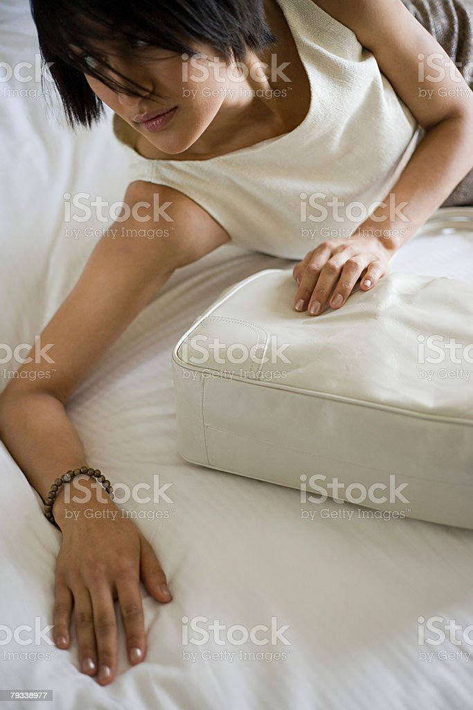 Young woman on bed with handbag 免版稅 stock photo