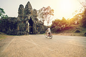 Young woman traveling in Cambodia visiting the temples of Angkor wat complex by bicycle. People travel discovery Asia concept. Shot at sunset, one woman only, adventure and exploration in Siem Reap, Southeast Asia.