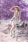 istock Young woman on bicycle in fantasy pink forest 801667426