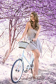 istock Young woman on bicycle in fantasy pink forest 801667440