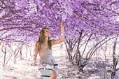 istock Young woman on bicycle in fantasy pink forest 801667444