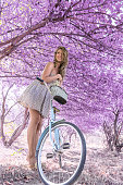 istock Young woman on bicycle in fantasy pink forest 801667448