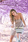 istock Young woman on bicycle in fantasy pink forest 801667452