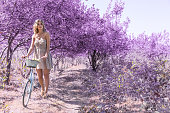 istock Young woman on bicycle in fantasy pink forest 801667464