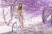 istock Young woman on bicycle in fantasy pink forest 801667468