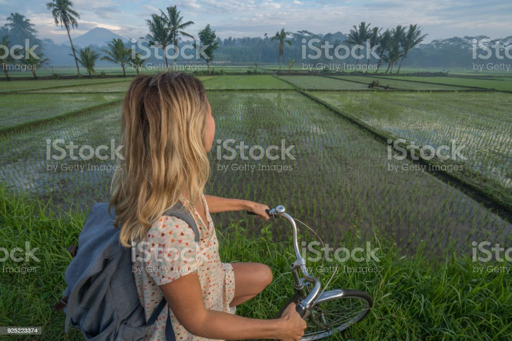 Young woman on bicycle stops to admire rice fields, Indonesia stock photo