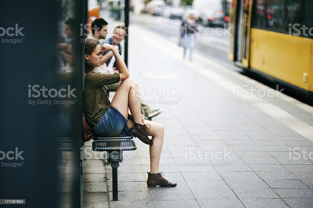 Junge Frau auf der Bushaltestelle – Foto
