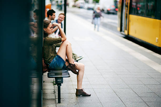 Young woman on bus stop stock photo