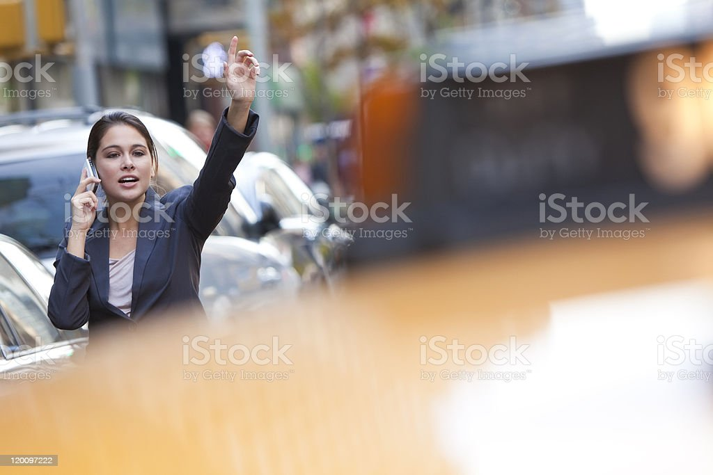 Young Woman on Cell Phone Hailing a Yellow Taxi Cab stock photo