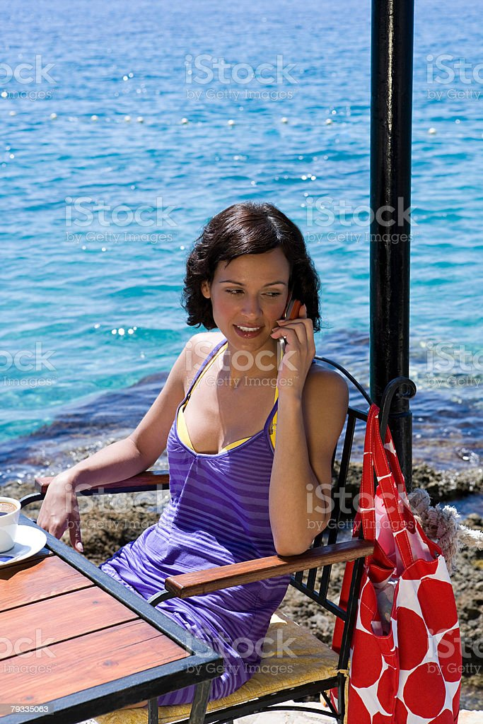 Young woman on cellphone by the sea 免版稅 stock photo
