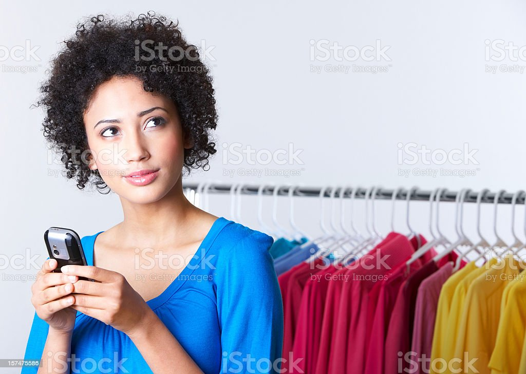 Young woman on cellphone shopping for clothes royalty-free stock photo