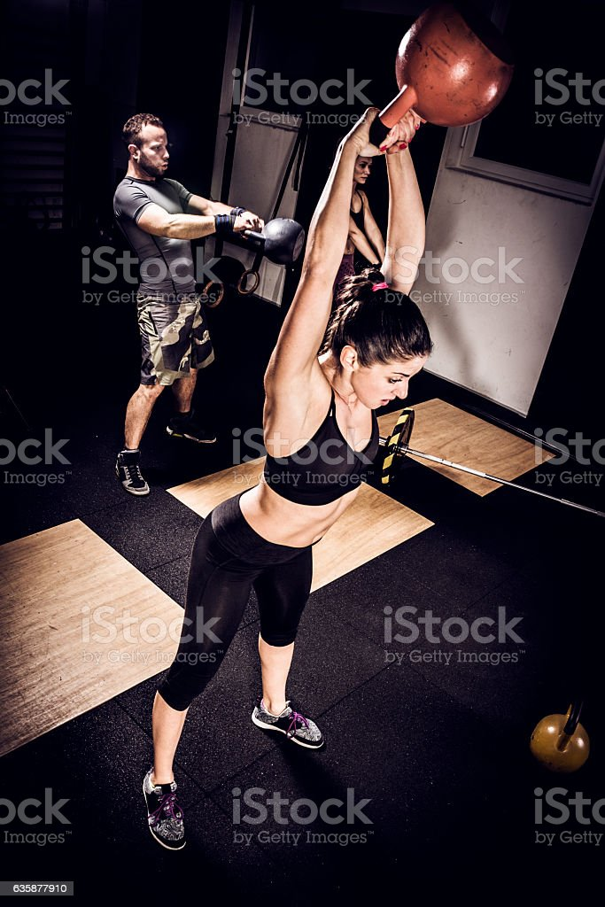 Young woman on cross training with kettlebell in gym stock photo
