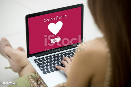 Young beautiful single woman browsing online dating website using laptop. Attractive Caucasian woman model sitting on sofa with notebook, searching for new love on-line. Close-up. Back view