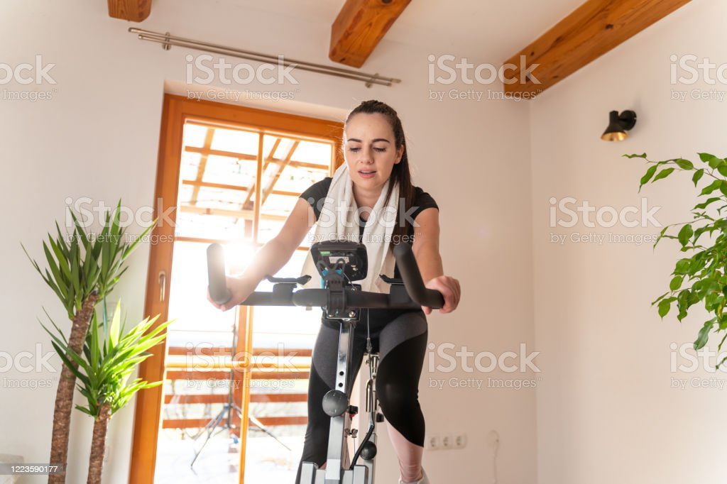 Young woman on exercise bike at home Three-quarter length shot of a young woman in sportswear with a black ponytail exercising on exercise bike at home 20-29 Years Stock Photo