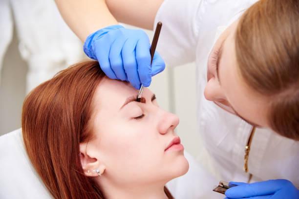 young woman on eyebrow correction in cosmetology clinic. - barwnik zdjęcia i obrazy z banku zdjęć